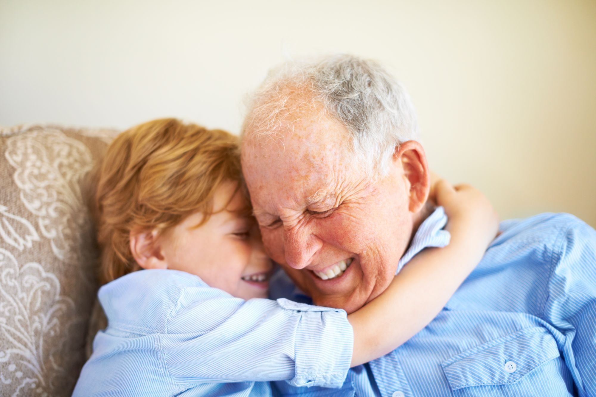 Young boy gives hug around the neck to Flourish Senior Living memory care resident