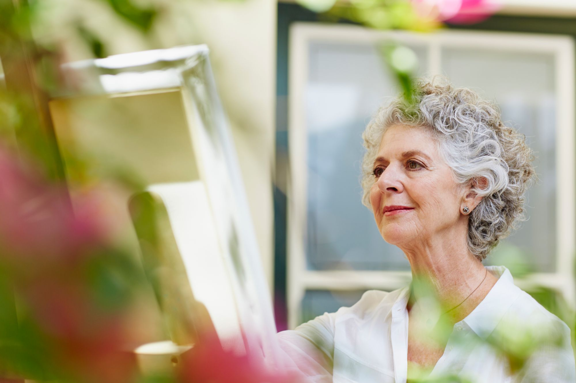 Senior living resident paints at an easel in the outdoors