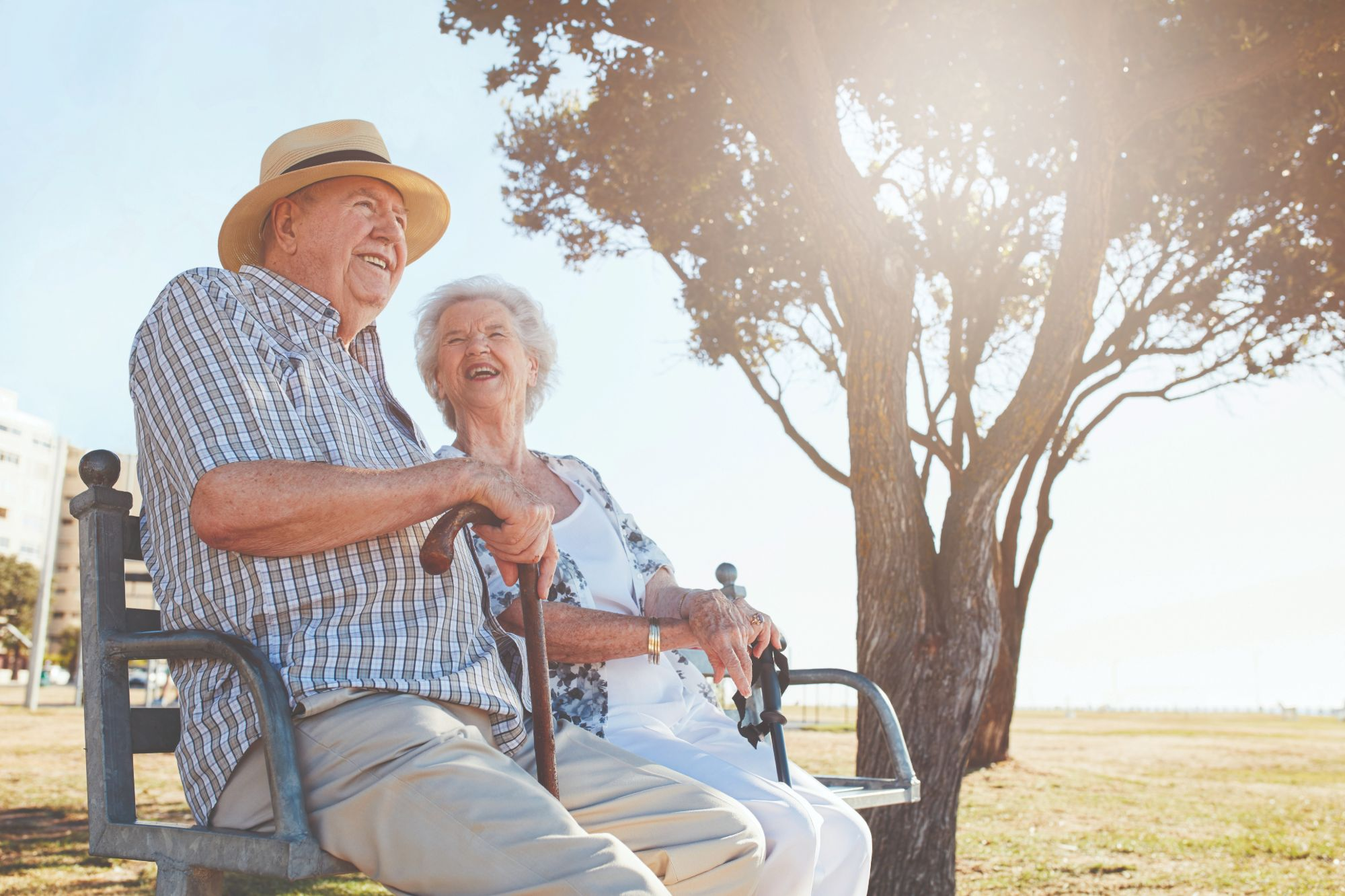 Male and female Flourish Senior Living residents smile and sit together on an outdoor bench next to a tree