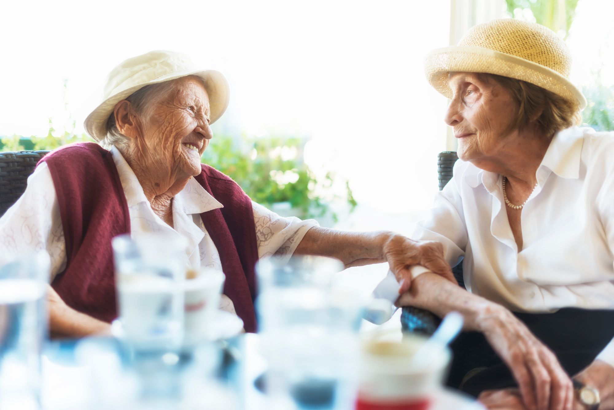 Senior Living residents holding the arm of another older woman as they sit wearing hats at an outdoor dining table and smile