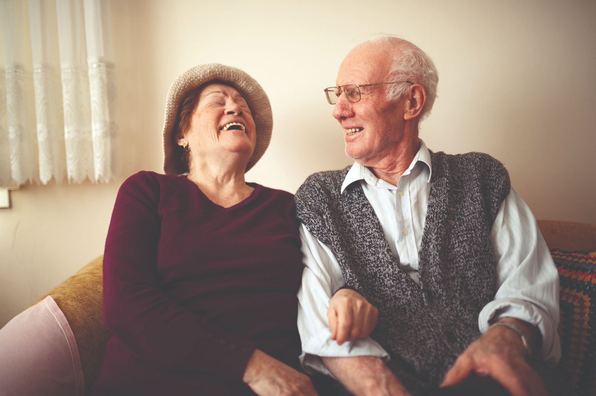 Black and white view of older man and woman sitting next to each other on couch and smiling