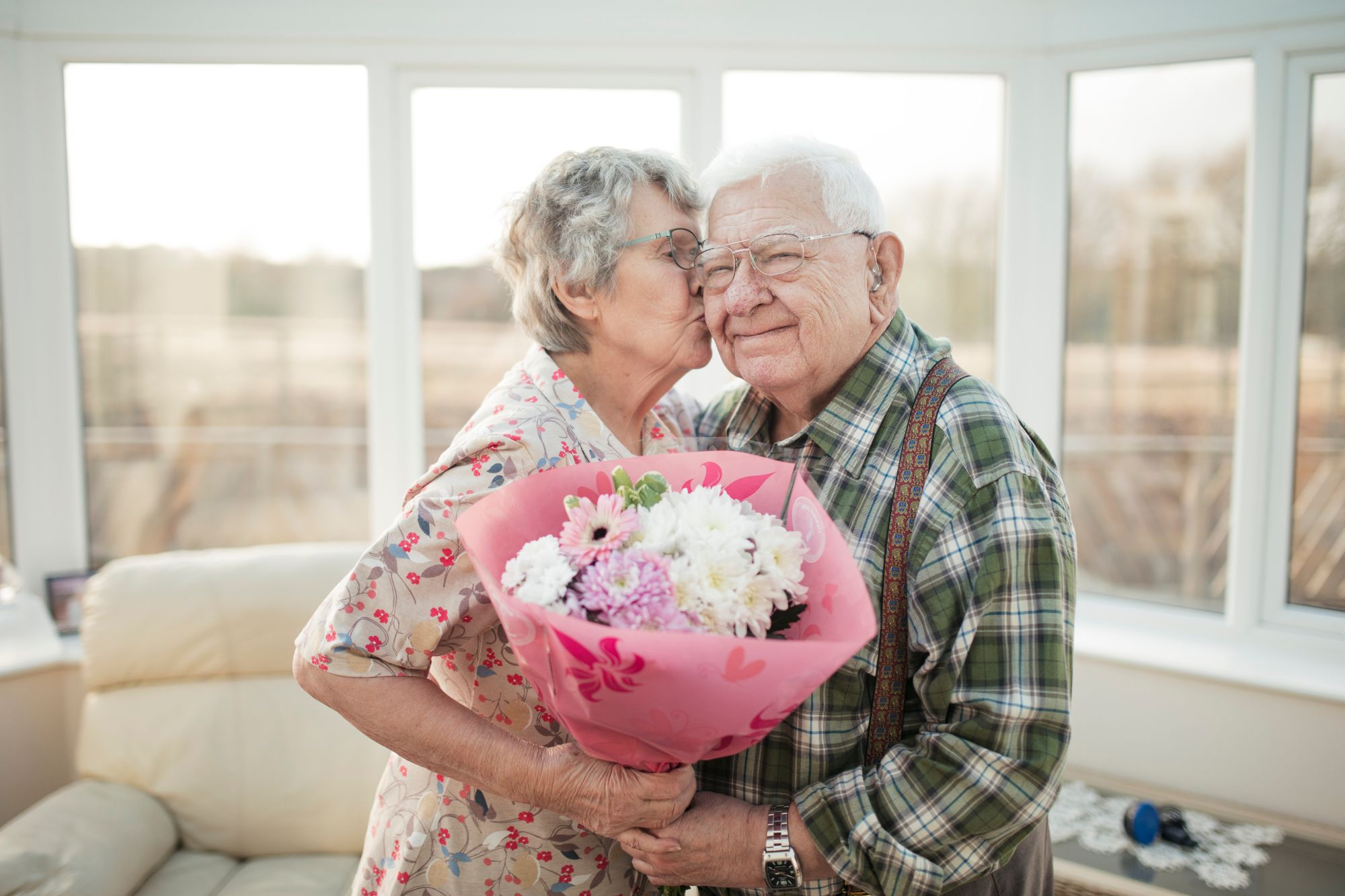 Senior aged female gives a kiss on the cheek to older male while they hold a flower bouquet in front of a large window