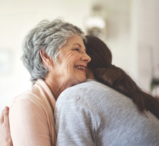 Black and white view of woman giving a hug to smiling older woman